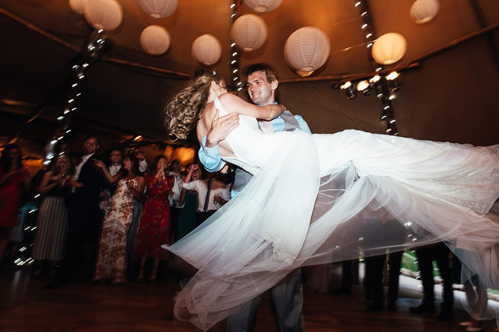 Groom scoops up his new bride for their first dance together