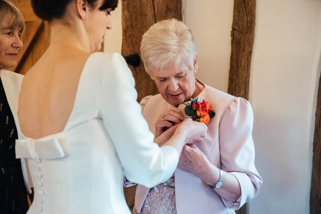 Bride pins on her mothers wedding corsage
