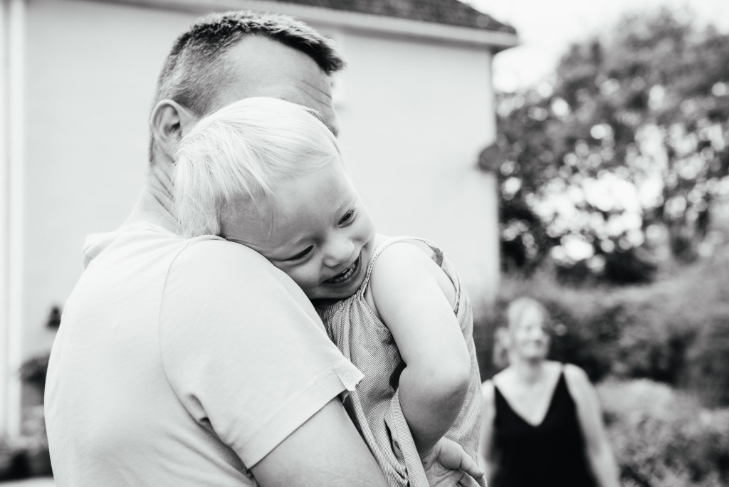 Black and white image of father and daughter smiling