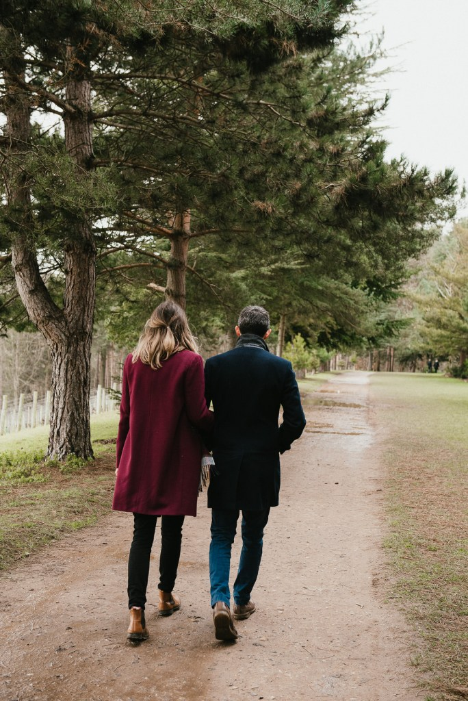 Couple walk together in the woods of Painshill Park