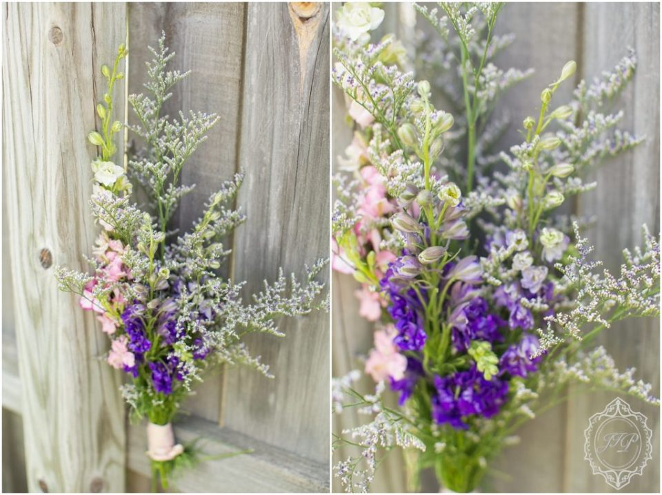 A grouping of wild flowers by Deloache Florals sits on a wooden fence.