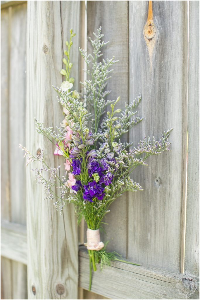 Purple, pink, and green wildflowers sit in a bouquet formation on a wooden fence. Florals by Deloache Florals