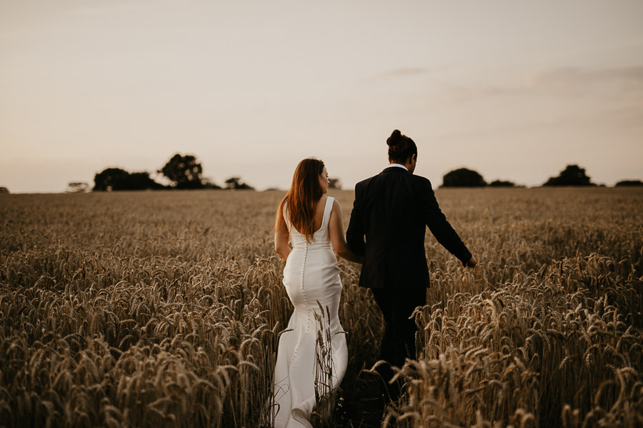 Bride and Groom walking through a wheat field at Mythe Barn