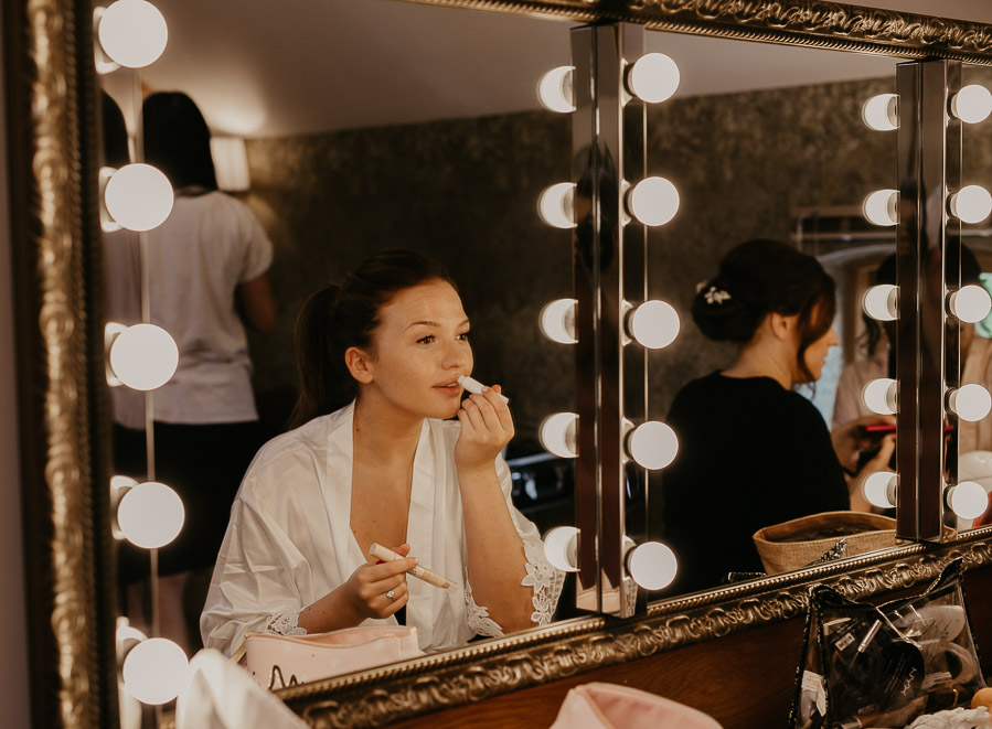 Bride putting on makeup in the mirror
