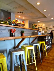 The restaurant has a modern design with rich wood tones contrasting the metal seating and exposed brick walls. Stools line bars around the edge of the space, with small tables through the center.