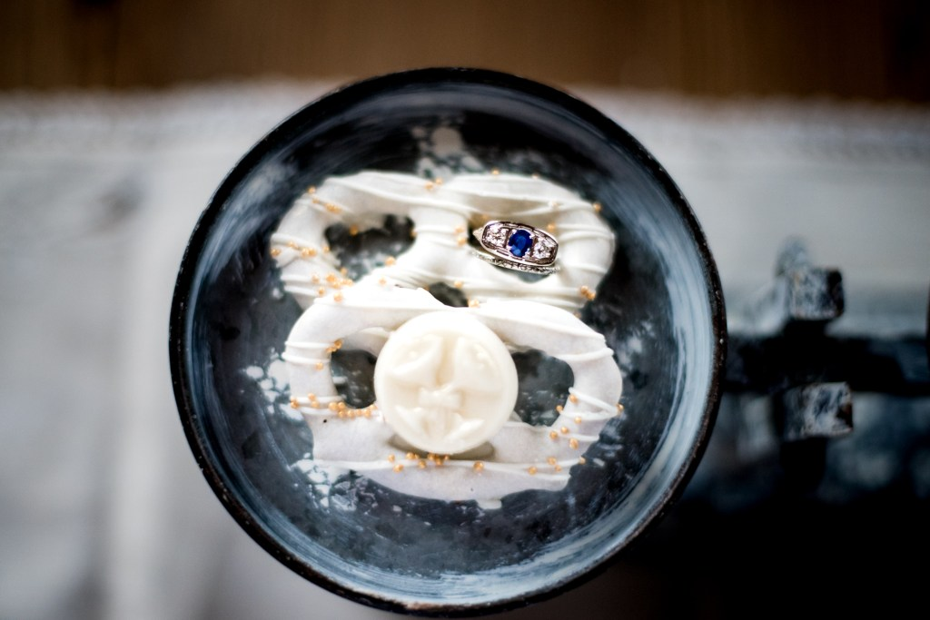 Jessica Patricia Photography white chocolate covered pretzel wedding favor with sapphire and diamond engagement ring on vintage scale