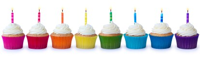 Row of brightly colored cupcakes decorated with candles