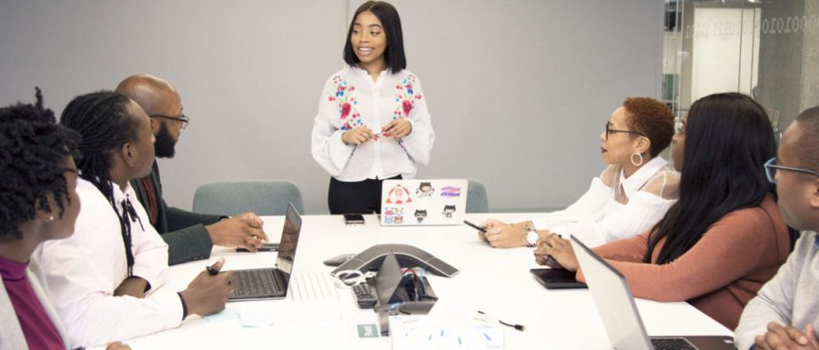 A young woman stands at the head of a conference table, while six meeting attendees look at her present during a content strategy lunch-and-learn.