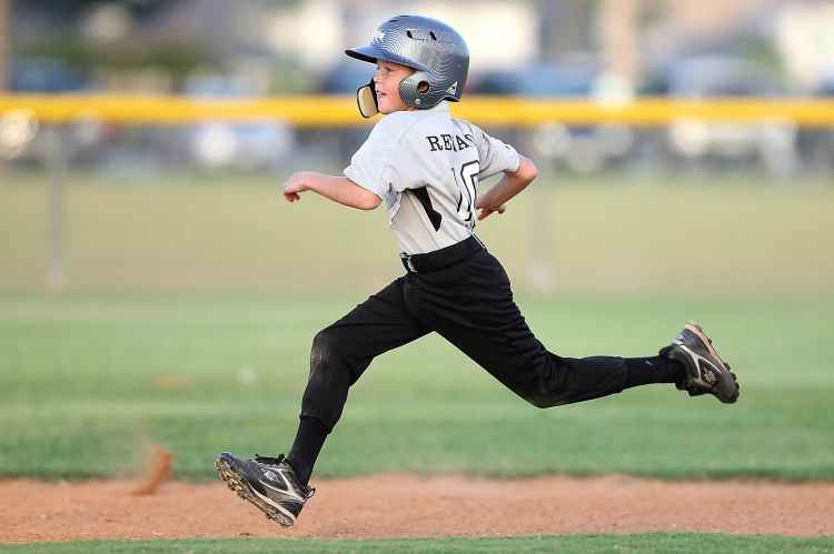 baseball player in gray and black uniform running in article about what parents should say at kids sports events to best support their child