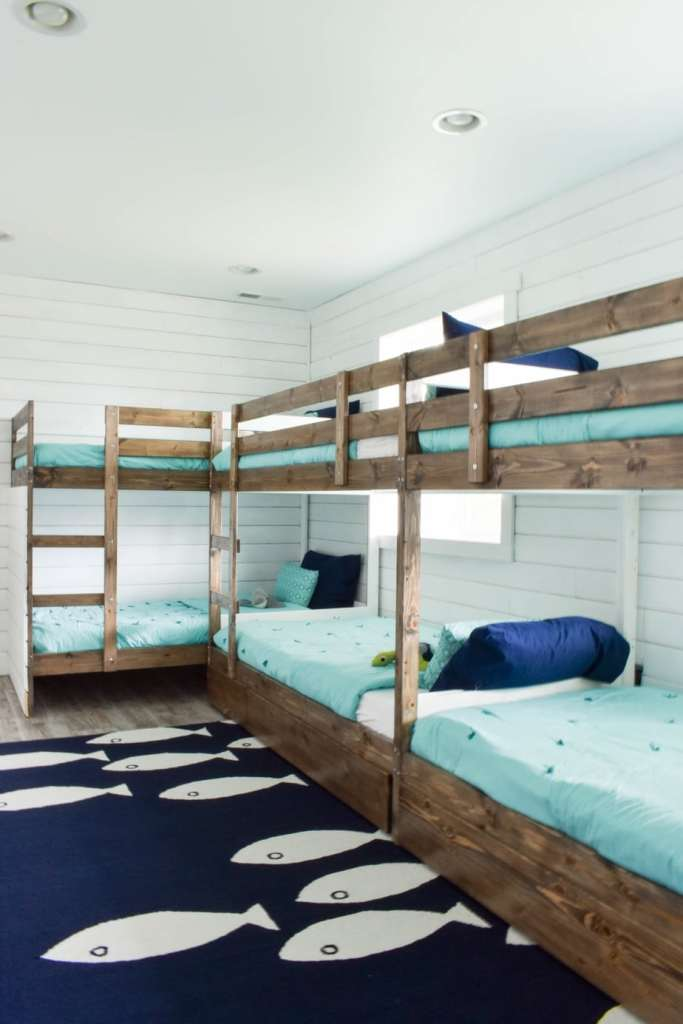 This fun ocean-themed beach house bunk room is the perfect vacation sleepover and play room for the kids. The Ikea MYDAL bunk beds have ladders and built-in storage.