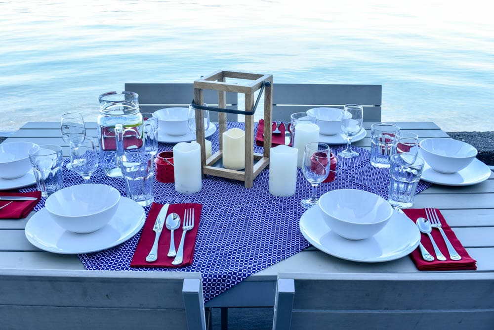 outdoor dining table set for an independence day party with red white and blue decorations and candles in front of water