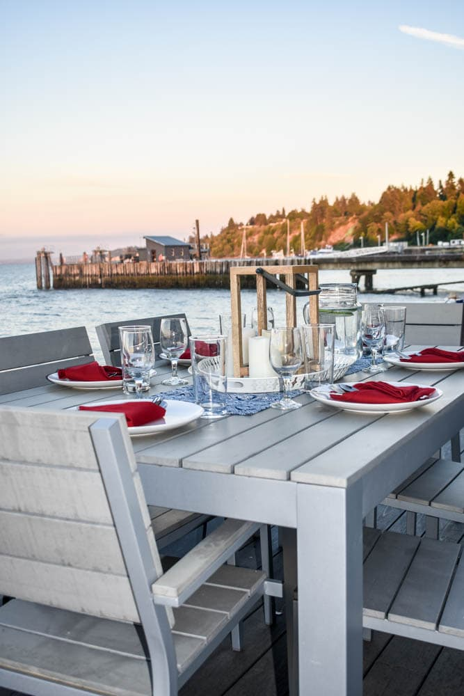 outdoor dining table set for a 4th of July party with a navy blue and white patterned table runner, red cloth napkins, candle lanterns, and a pier in the background