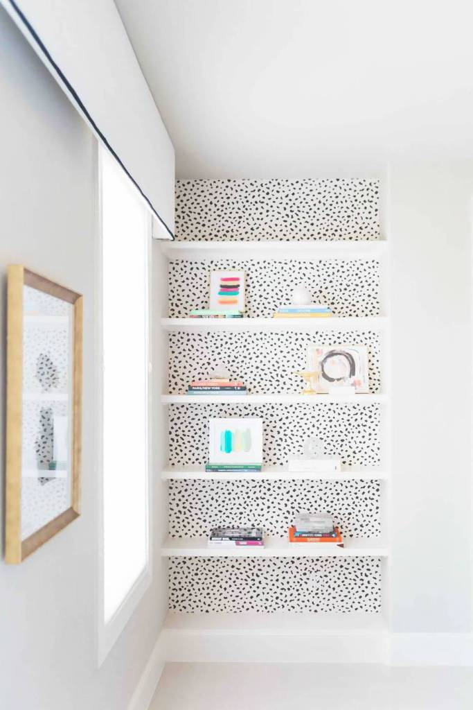 photo of built-in bookcase backed with speckled wallpaper