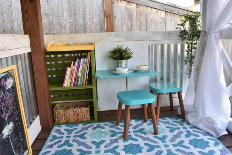 image of inside of playhouse with mini dining table and flisat stools, bookshelf, and chalkboard