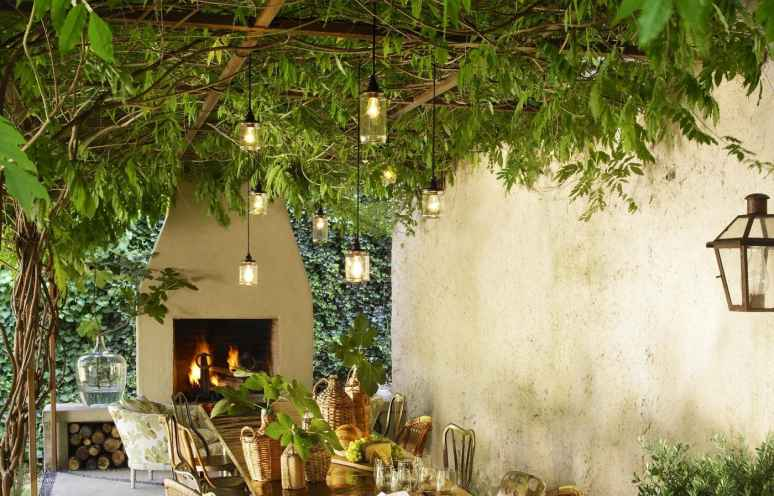 outdoor dining room with pergola covered in wisteria for patio shade, pendant lights, and an outdoor fireplace