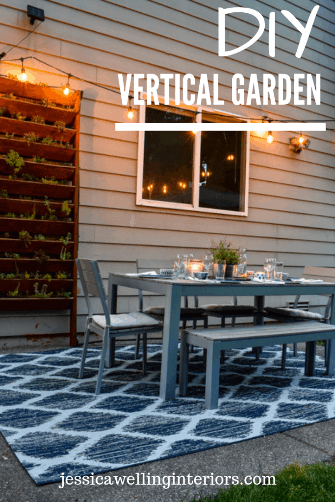 image of outdoor dining space at dusk with wood vertical garden in background and lit by string lights