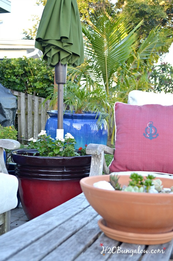 patio seating area with DIY planter umbrella stand and umbrella