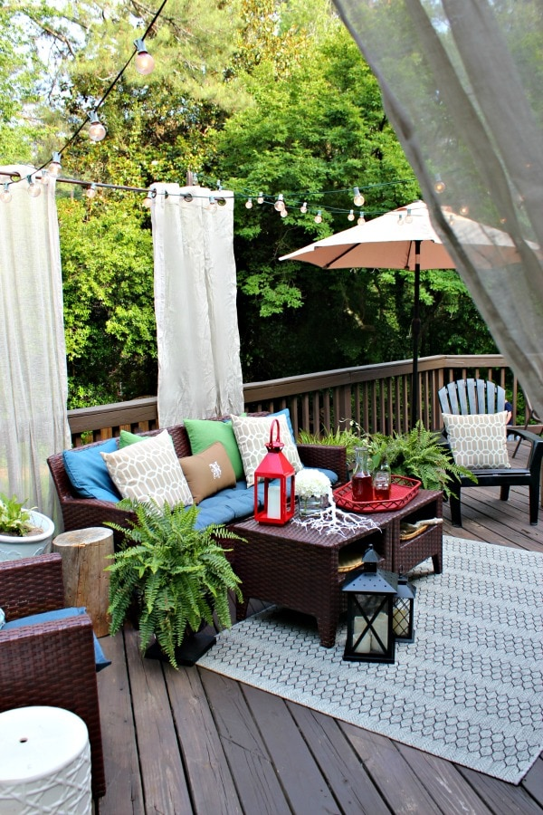 colorful deck seating area with outdoor curtains and string lights as a patio shade idea