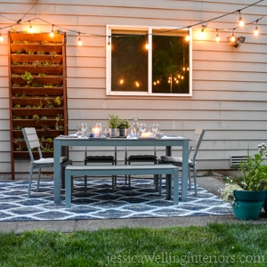 backyard patio with dining set, vertical garden, and string lights