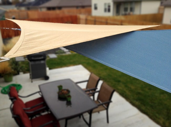 two overlapping shade sails over a patio dining space