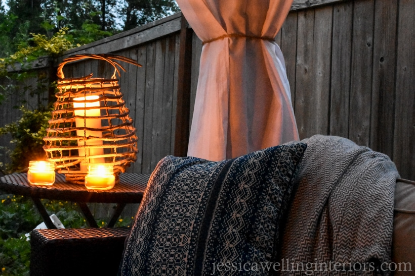 end of outdoor sofa and end table with glowing candle lanterns