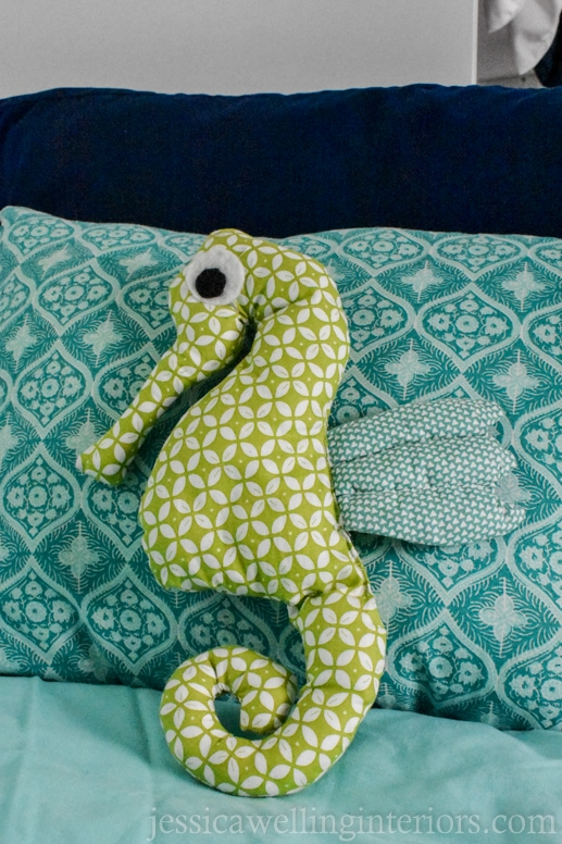 hand made stuffed seahorse toy on a child's pillow on a bunk bed