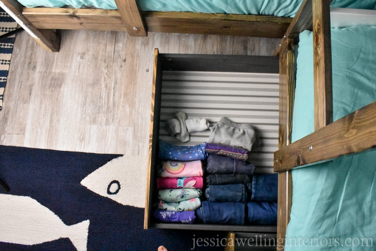 IKEA bunk bed room with HEMNES under-bed storage drawer hack. Drawer is pulled out with folded clothing inside