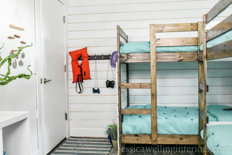 beach house bunk room with aqua bedding, and an entry way with storage hooks and a life jacket