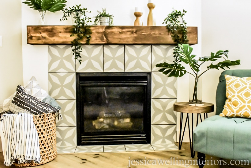 completed painted faux cement tile fireplace makeover with grey and white stenciled tile, new wood mantel, a basket with blankets and throw pillows, and a chair