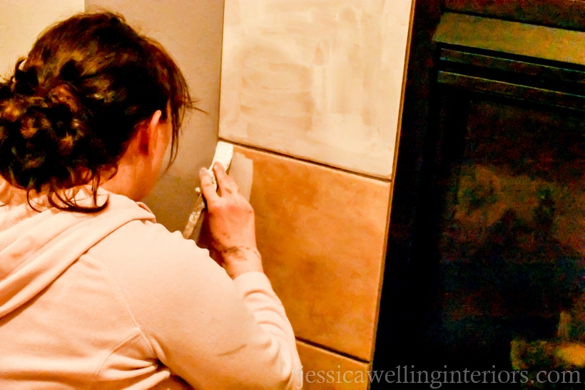 woman applying BIN primer to tile fireplace surround with a paintbrush before painting and stenciling tiles