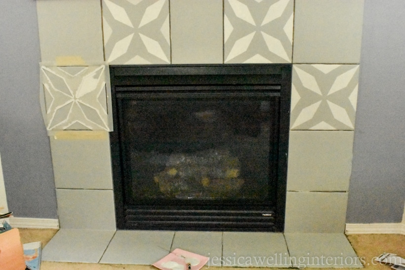 gas fireplace with surrounding tiles painted and a few of the tiles have been painted with a faux cement tile stencil