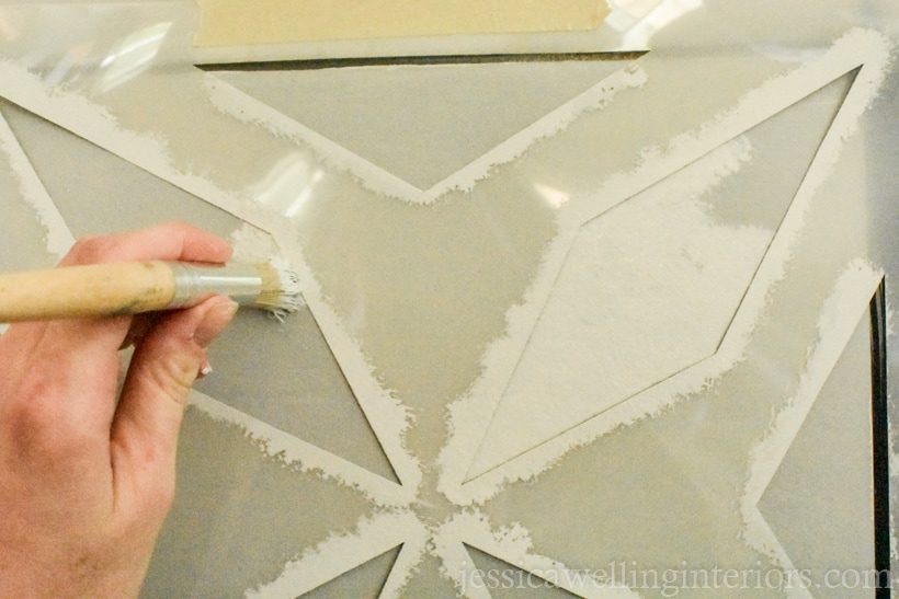 hand holding stencil paintbrush, dabbing paint onto tile to create a faux cement tile pattern