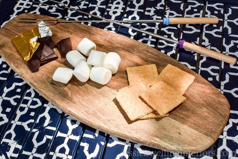 patio table with white patterns from furniture stencil with wood cutting board and s'more supplies