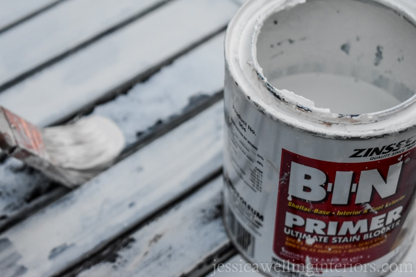 open can of Zinsser BIN primer sitting on rusty patio table, with paintbrush applying primer in the background