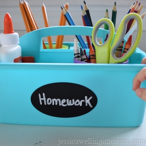 """aqua blue plastic caddy labeled """"Homework"""" and filled with colorful school supplies"""