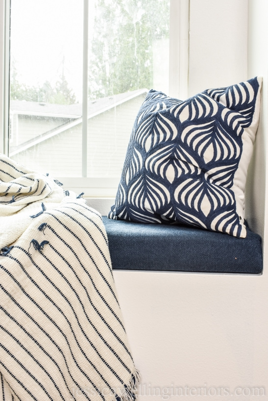close-up of DIY window seat cushion in kids bedroom with throw pillow and throw blanket