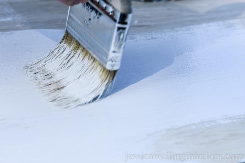 close-up of paintbrush applying BIN primer to top of DIY floating desk