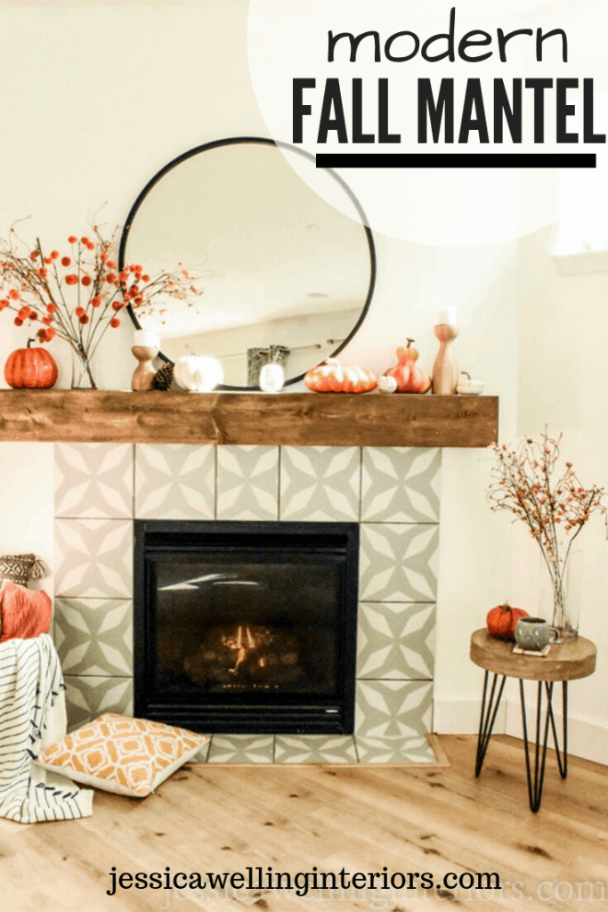 Modern Fall Mantel: image of mid-century modern fireplace with wood mantel decorated for Fall with round mirror, pumpkins, and Fall stems in a vase