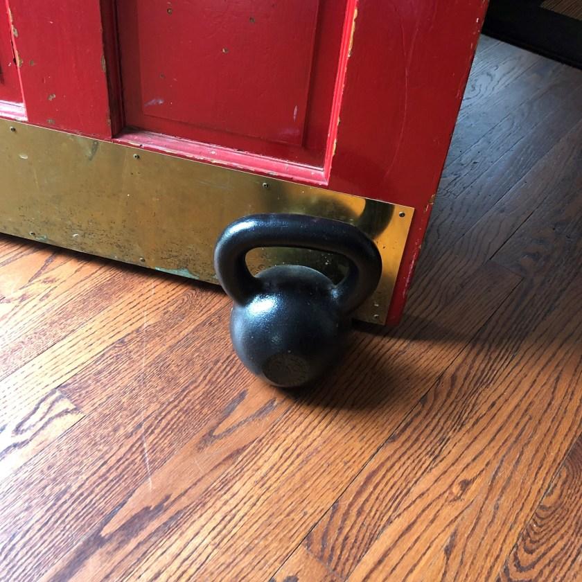 a kettlebell propping open a door