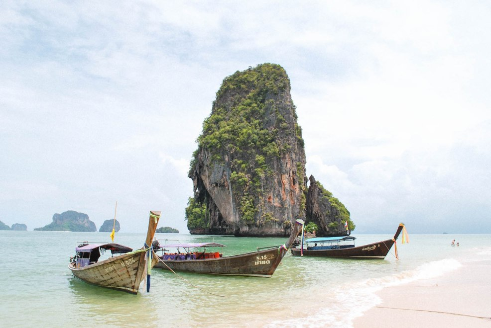 long tail boats and limestone cliffs at phra nang beach in Krabi thailand