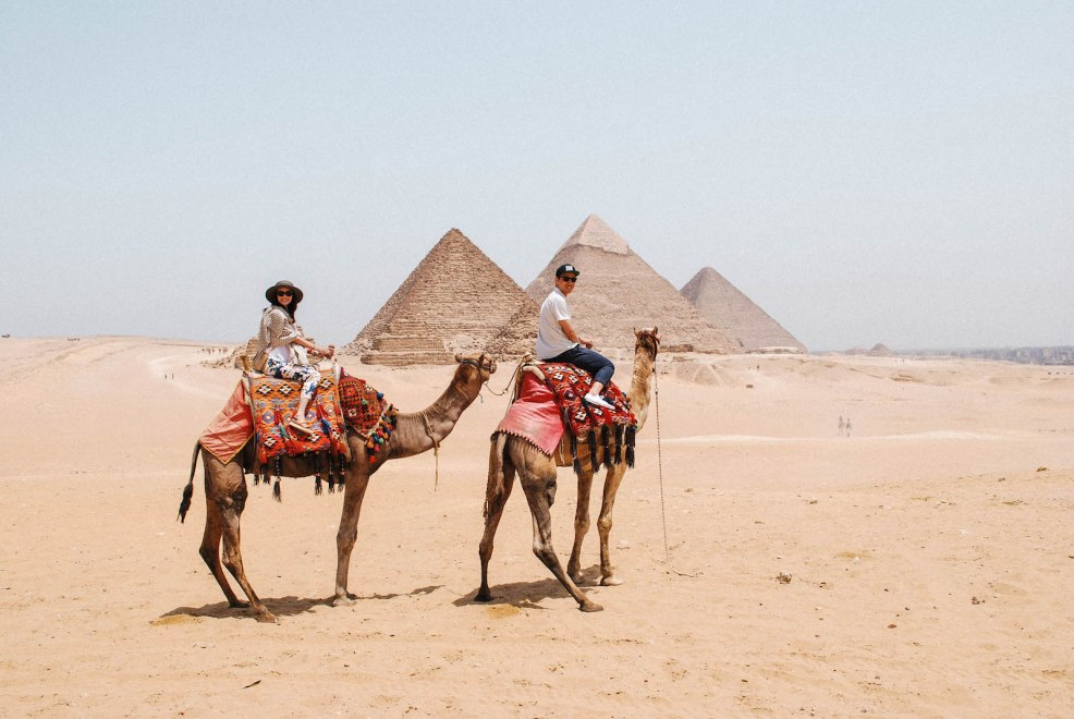 riding camels in front of the great pyramids of Giza in Cairo Egypt