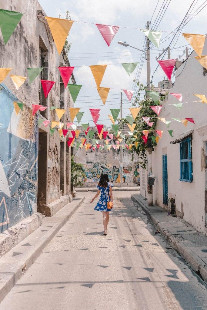 girl walking down colourful street in getsemani Colombia
