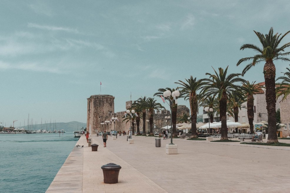 Promenade in Trogir with palm trees and medieval walls