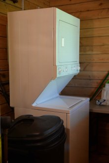 A wash and dryer is located next to the bathroom.