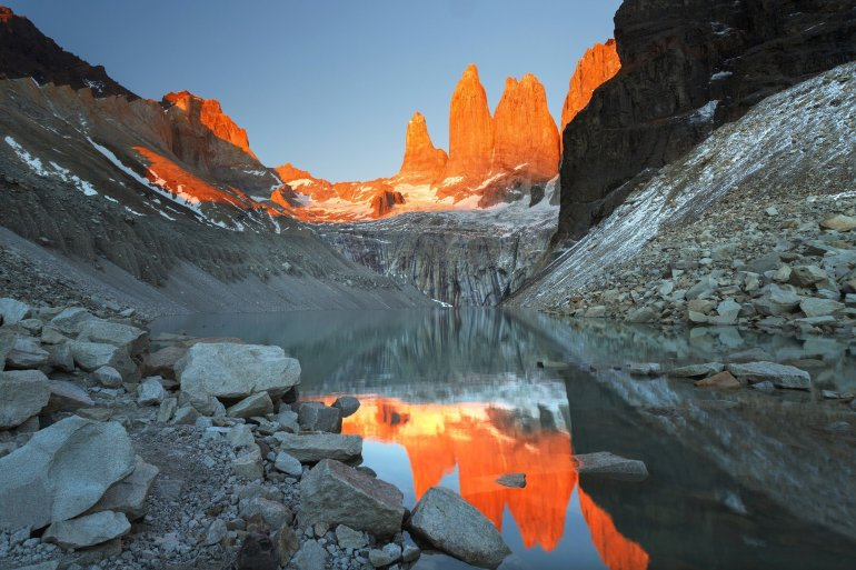 The rocky spires of the Torres are illuminated with an orange glow over a clear lake in the early morning.