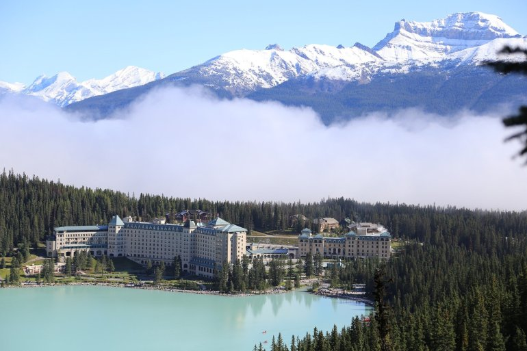 View of the Fairmont Hotel bordeing Lake Louise with a hazy cloud rolling in from the distance.