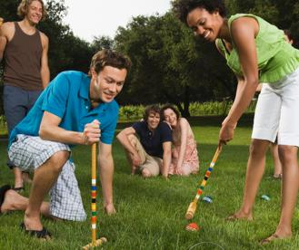 A group of friends playing croquet in their backyard staycation ideas.