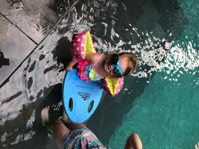 Happy kid in a pool with blue goggles on while on a staycation at home.