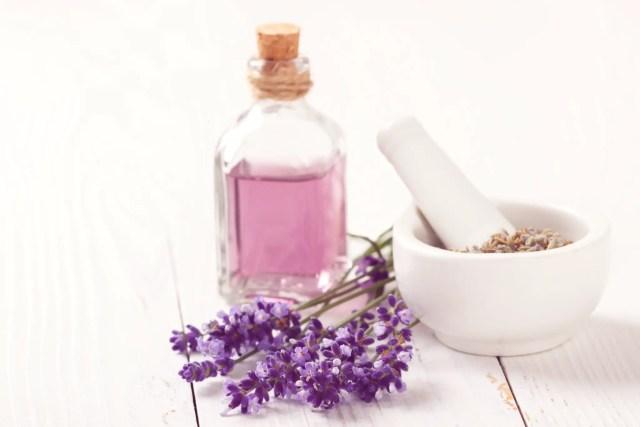 Purple lavender oil in a glass bottle, fresh lavender, and fresh lavender in a white bowl for a staycation spa day.