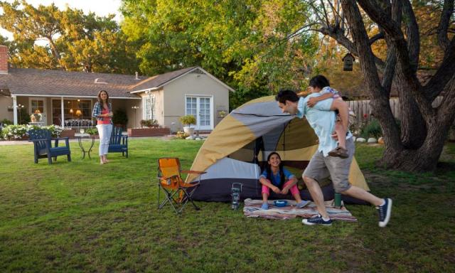 Mom and dad with two kids playing in the backyard with a tent set up for backyard camping.